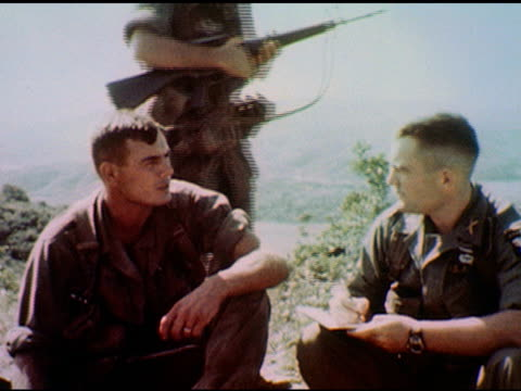 / two officers seated, vietnam landscape in background - one asks the other about brigade success / another soldier or officer approaches and joins... - other stock videos & royalty-free footage