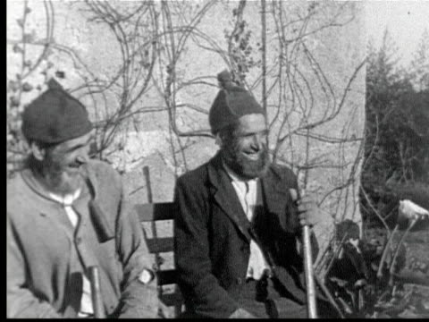 two old men w/ beards wearing pointed knitted hats sit on bench / funchal, madeira - anno 1925 video stock e b–roll