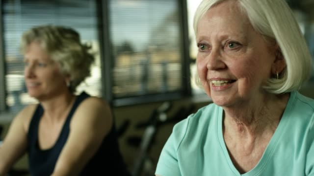 two older white women at exercise class at the gym - practicing stock videos & royalty-free footage