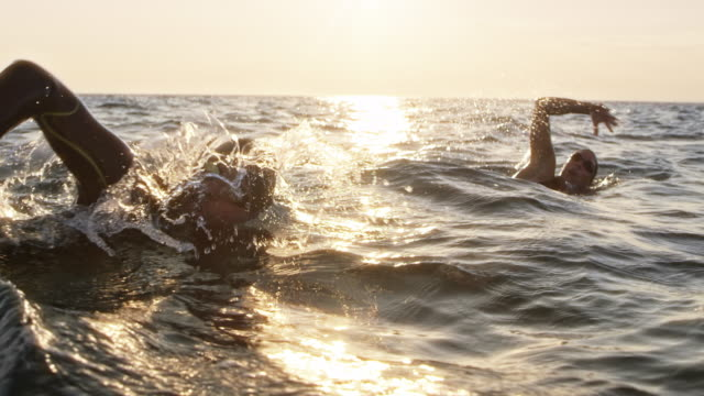 slo mo ts two open water swimmers swimming front crawl at choppy sea in sunshine - competizione video stock e b–roll