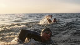 SLO MO TS Two open water swimmers swimming front crawl at sea in sunshine
