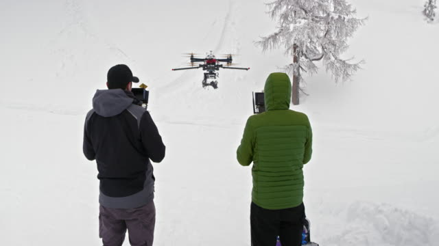Two operators flying a drone in winter conditions
