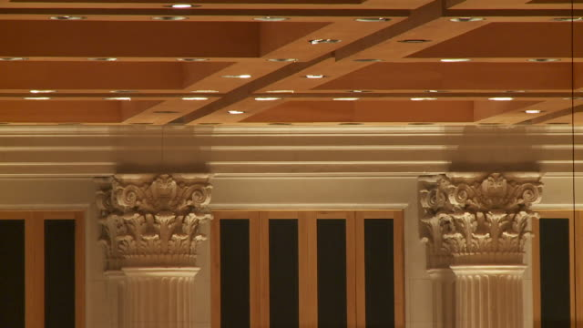 Two ornate columns support a beautiful ceiling in a concert hall.