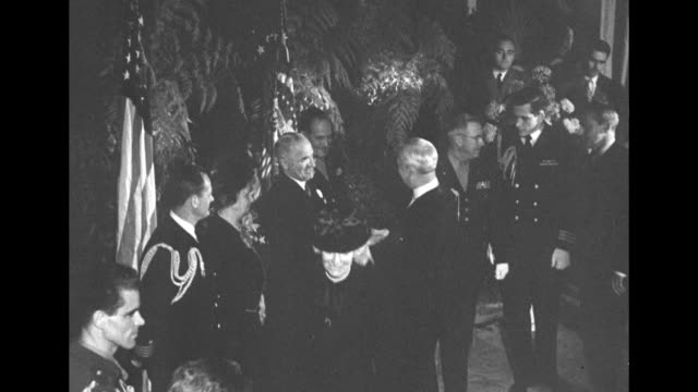Two overhead shots of Pres Harry Truman and wife Bess in receiving line in room at WaldorfAstoria hotel shaking hands with guests / closer shot of...