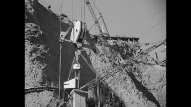 two overhead shots of wooden footings of foundation of dam on canyon floor / dump truck backed up to concrete mixing plant / large bucket carrying... - hoover staudamm stock-videos und b-roll-filmmaterial