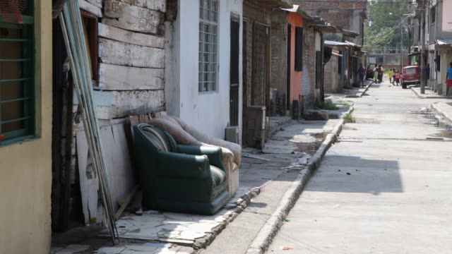 two padded armchairs placed next to a house wall on the left side of a street in the background children can be seen in the middle of the empty street - america del sud video stock e b–roll