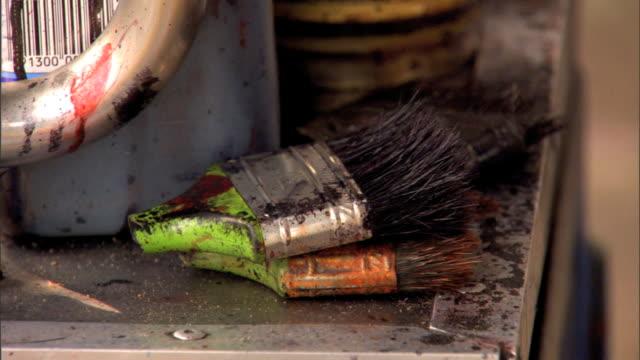 MCU Two paintbrushes without handle on table outside unidentifiable male hand picking up a brush Boot polisher shoe polish bootblacks shoeshiner