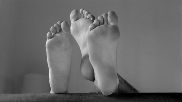 Two pairs of bare feet engage in a game of footsie.
