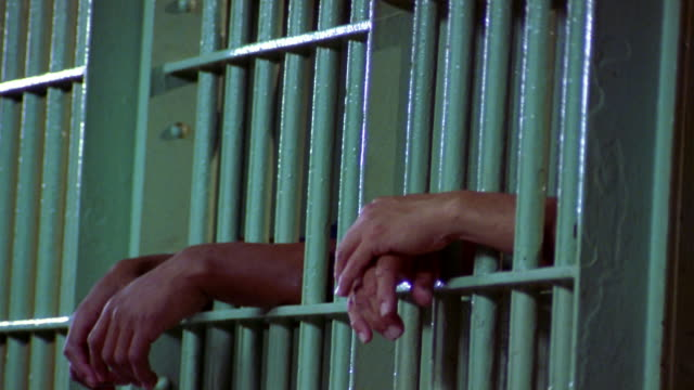vídeos de stock e filmes b-roll de wide shot two pairs of black and caucasian male hands resting on prison cell bars - preso