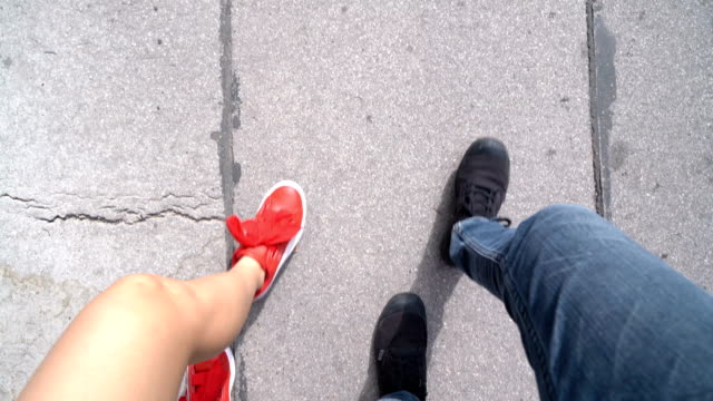 pov two pairs of shoes walking on the street - coordinazione video stock e b–roll
