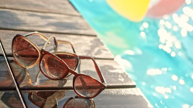 two pairs of sunglasses on the side of the pool in sunshine - pair stock videos & royalty-free footage