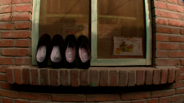 vídeos y material grabado en eventos de stock de cu two pairs of traditional black chinese shoes airing on windowsill, beijing, china - cuatro objetos