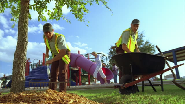 ws zi zo slo mo two park maintenance workers landscaping with mulch / kyle, texas, usa - wheelbarrow stock videos and b-roll footage