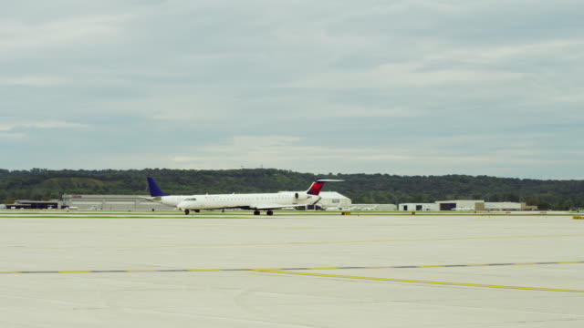 Two passenger jets eclipse one another as they taxi across the runways at an airport.