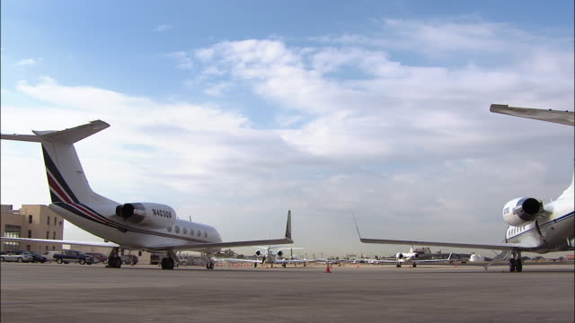 two passenger jets sit parked on the tarmac at louis armstrong new orleans international airport. - 飛行機格納庫点の映像素材/bロール