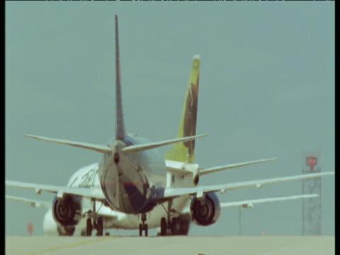 stockvideo's en b-roll-footage met two passenger jets taxi in heat haze, denver airport - dia
