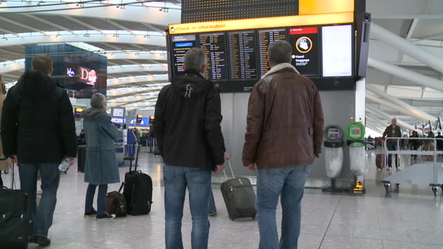 two passengers stare at a flight departure board as flights are delayed because of air traffic control problems rear view with no identification - air traffic control点の映像素材/bロール