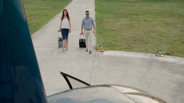 two passengers with luggage approaching helicopter - partire video stock e b–roll