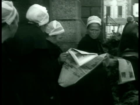 two peasant men walking reading newspaper women in white caps reading newspapers [could be underground passeurs le chambonsurlignon] radio towers... - 1938 stock videos & royalty-free footage