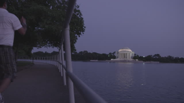 ws two pedestrians stroll along banks of the potomac river at dusk with jefferson memorial in background / washington dc, united states - jefferson memorial stock videos and b-roll footage