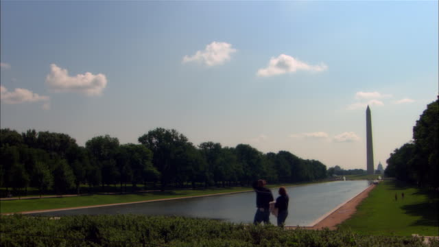 ws two people at mall pool, washington monument in background, washington dc, usa - washington monument stock videos & royalty-free footage