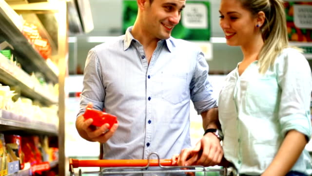 Two people buying cheese in supermarket.