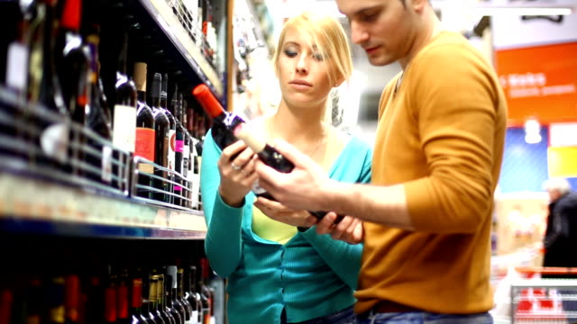 Two people buying wine in supermarket.