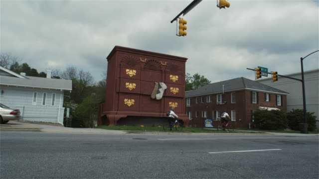 LA WS Two people cycling past huge chest of drawers along street / High Point, North Carolina, USA