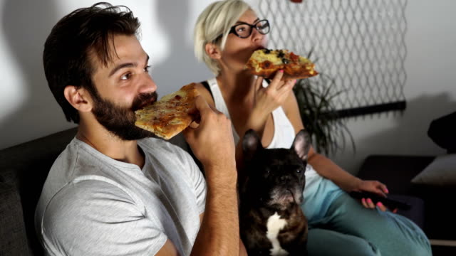 two people eating pizza and watching tv - sofa stock videos & royalty-free footage