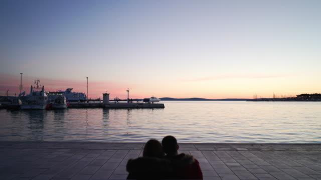 Two people embrace at Split Croatia Harbor at late sunset, dusk