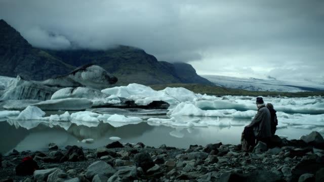vídeos de stock e filmes b-roll de two people enjoying glacier lagoon - distante