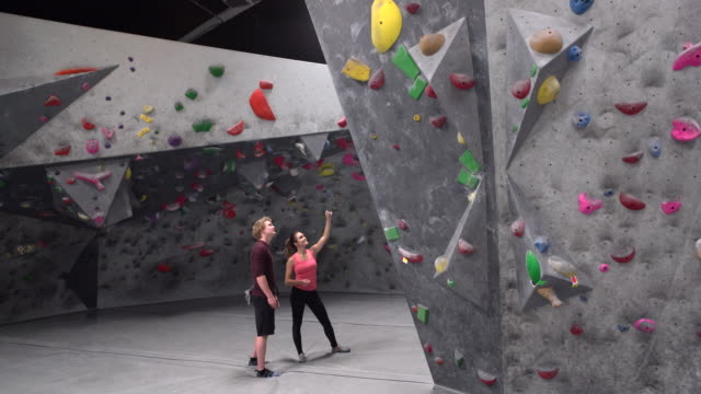 ws two people getting ready to climb a climbing wall - climbing wall stock videos & royalty-free footage