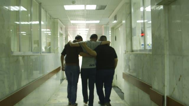 two people help friend walk through baghdad hospital - lesionato video stock e b–roll