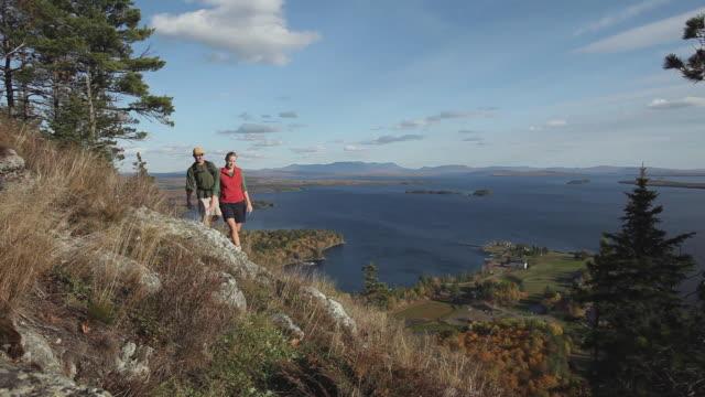 ws tu ha two people hiking on mt kineo with moosehead lake in background, maine, usa - berretto da baseball video stock e b–roll