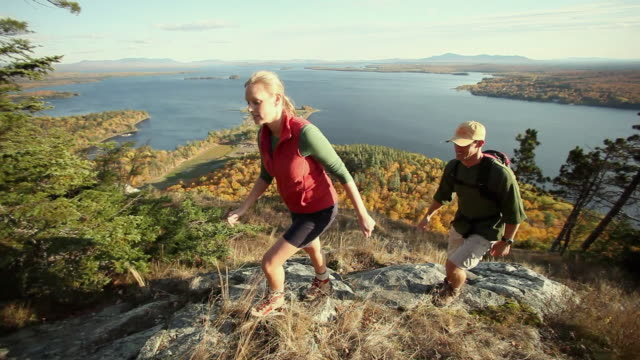 WS PAN HA Two people hiking on Mt Kineo with Moosehead Lake in background, Maine, USA