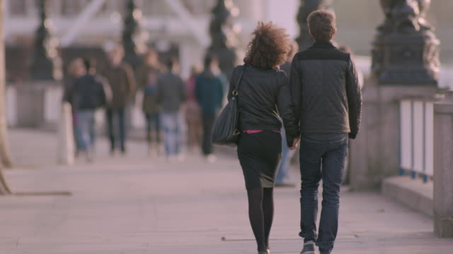two people holding hands walk along the embankment on a wintry day, london, uk. - holding hands stock videos & royalty-free footage