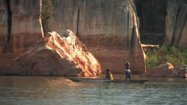 ws, pan, two people in dugout canoe moving down river with limestone cliffs rising above, taolanaro, toliara province, madagascar - river stock videos & royalty-free footage