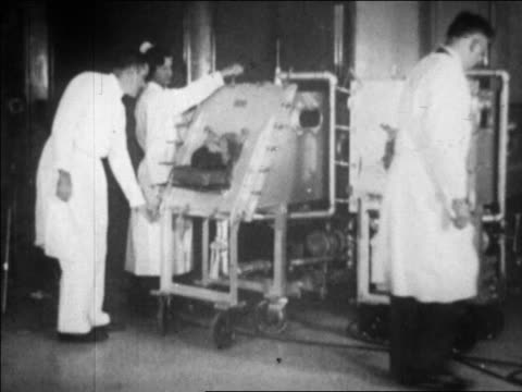 two people in iron lungs in hospital / boston / newsreel - 1920 1929 stock-videos und b-roll-filmmaterial