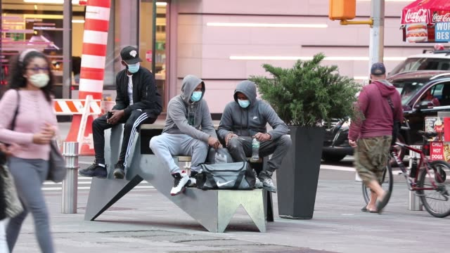 two people in masks and a hoodie sit as pedestrians, some in face masks, traverse times square on october 19, 2020 in new york city. a state order... - sitting stock videos & royalty-free footage