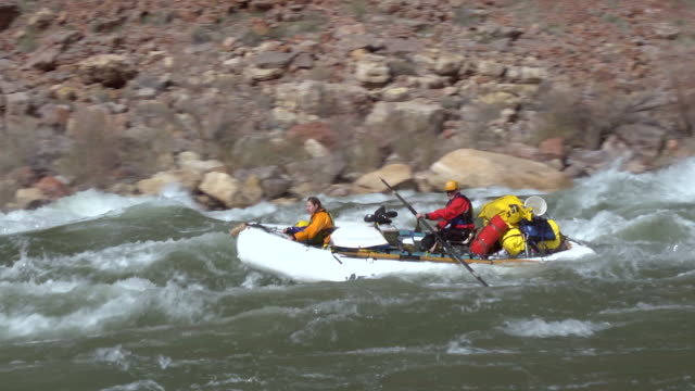ws pan zi two people in white raft floating down rapid and rocky shore in background / grand canyon, arizona, usa - grand canyon national park stock videos & royalty-free footage