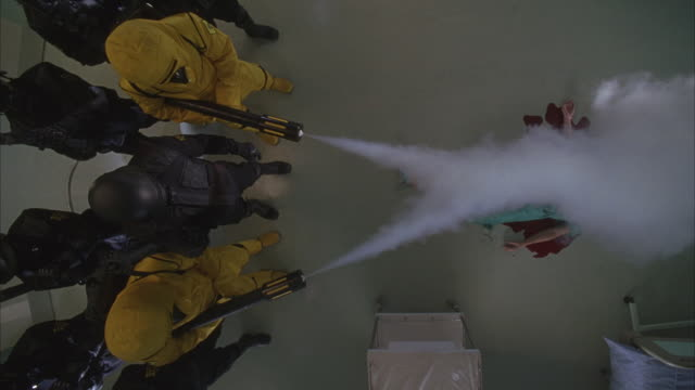 Two people in yellow protective suits shoot streams of a gaseous material over a body lying on the floor.