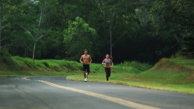 stockvideo's en b-roll-footage met two people jogging on the side of the road - elasthaan