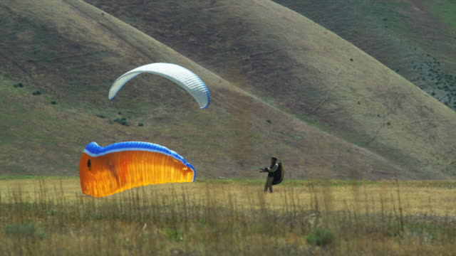 ws two people landing after paragliding / lehi, utah, usa. - lehi stock videos & royalty-free footage