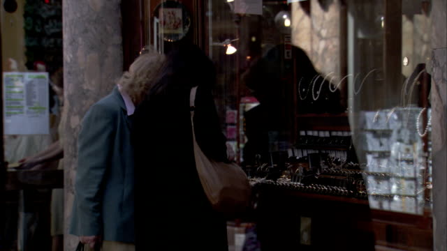two people look through the window of a jewelry shop in liverpool, england. - jewellery stock videos & royalty-free footage