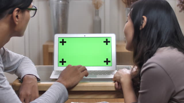 Two people looking at laptop with green screen