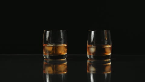 two people makes a toast with whiskey black background - honour stock videos & royalty-free footage