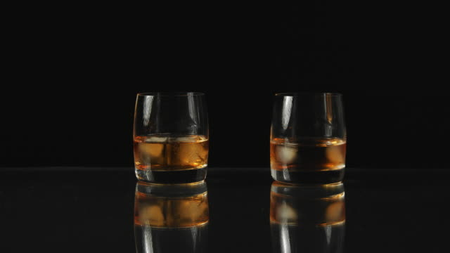 two people makes a toast with whiskey black background - refreshment stock videos & royalty-free footage
