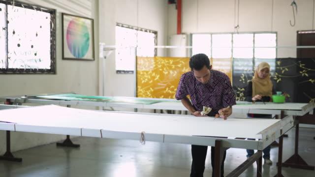 two people making batik in a workshop - batik stock videos and b-roll footage
