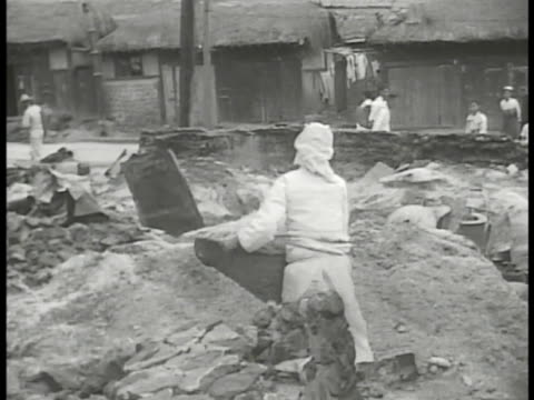 two people manually clearing inside of bombedout building in korea town moving basket to pile un forces injured us soldier being helped onto... - korean war stock videos & royalty-free footage