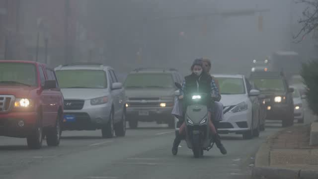 two people on a moped ride through thick fog on north avenue during the coronavirus pandemic on december 12, 2020 in baltimore, maryland. in maryland... - two people stock videos & royalty-free footage